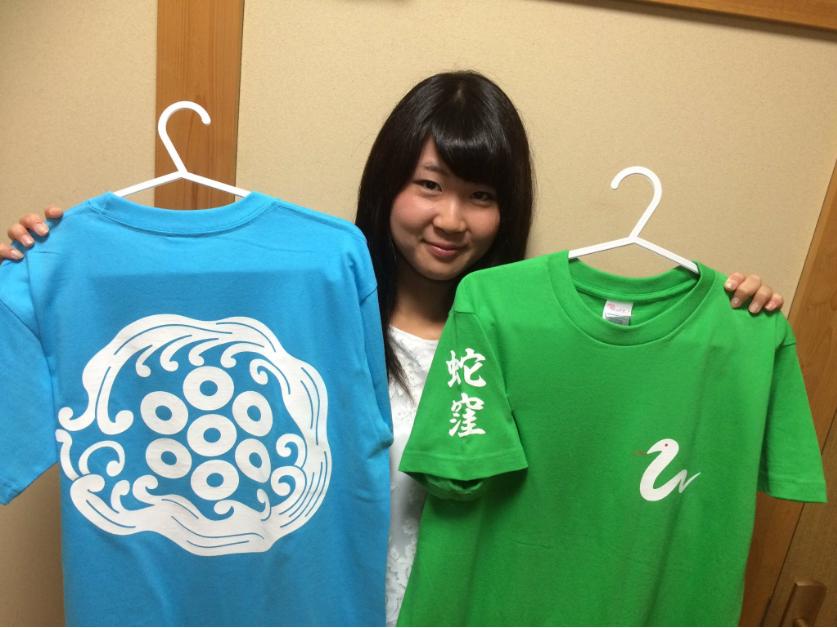 「蛇窪Tシャツ」を持つ上神明天祖神社の巫女さん