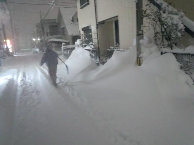大雪の最中、雪かきに向かう人