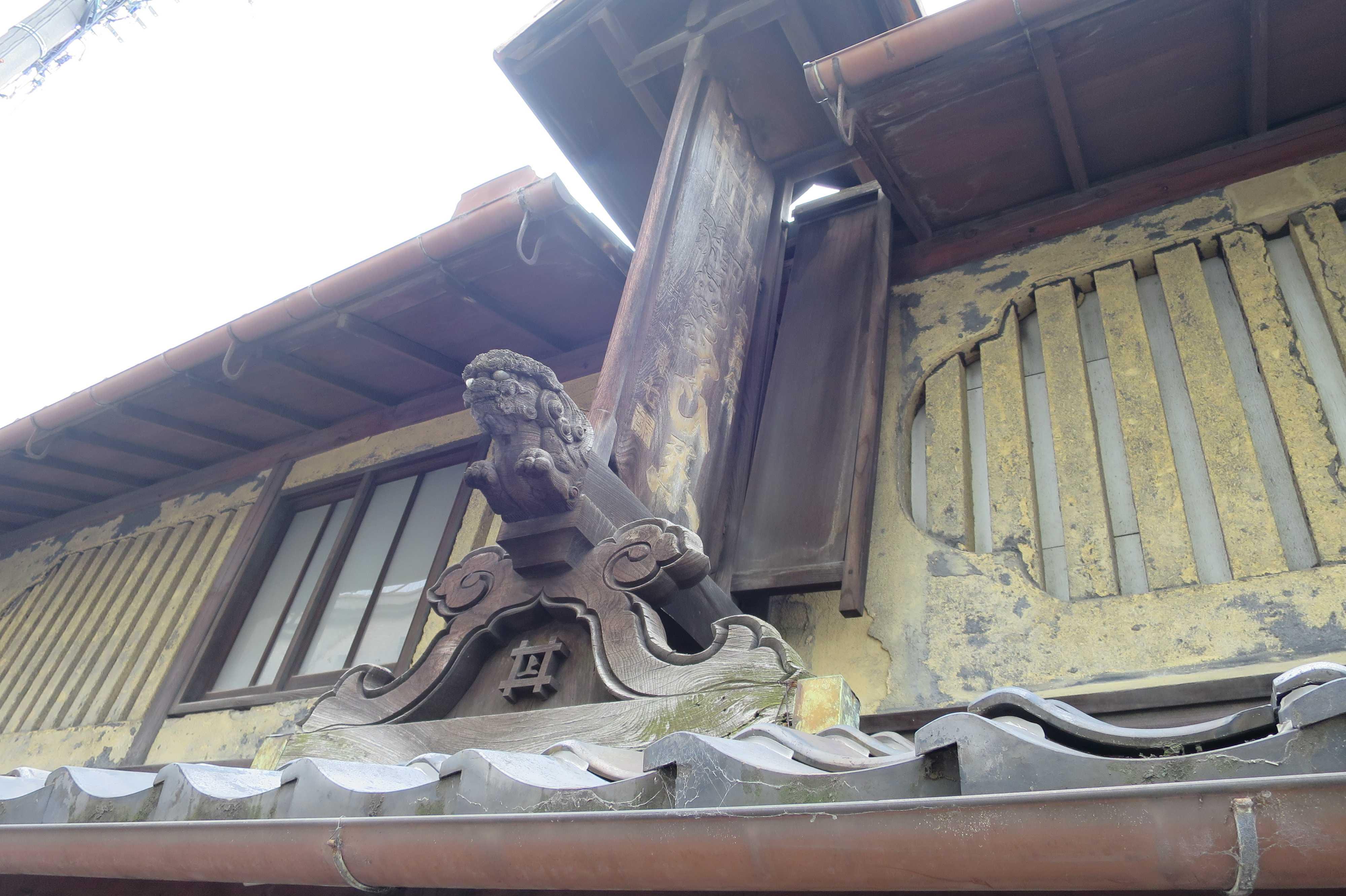 雨除け付きの古い看板と虫籠窓(京都市下京区の井上清七薬房)