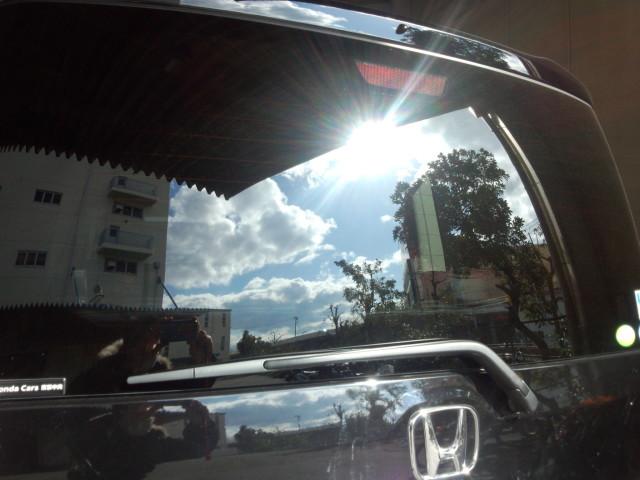 車のリアウィンドウに映り込む太陽