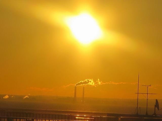 煙を棚引かせる煙突とオレンジ色の朝日