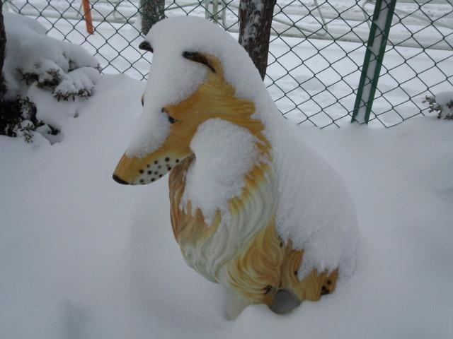 雪に埋もれる犬の置物