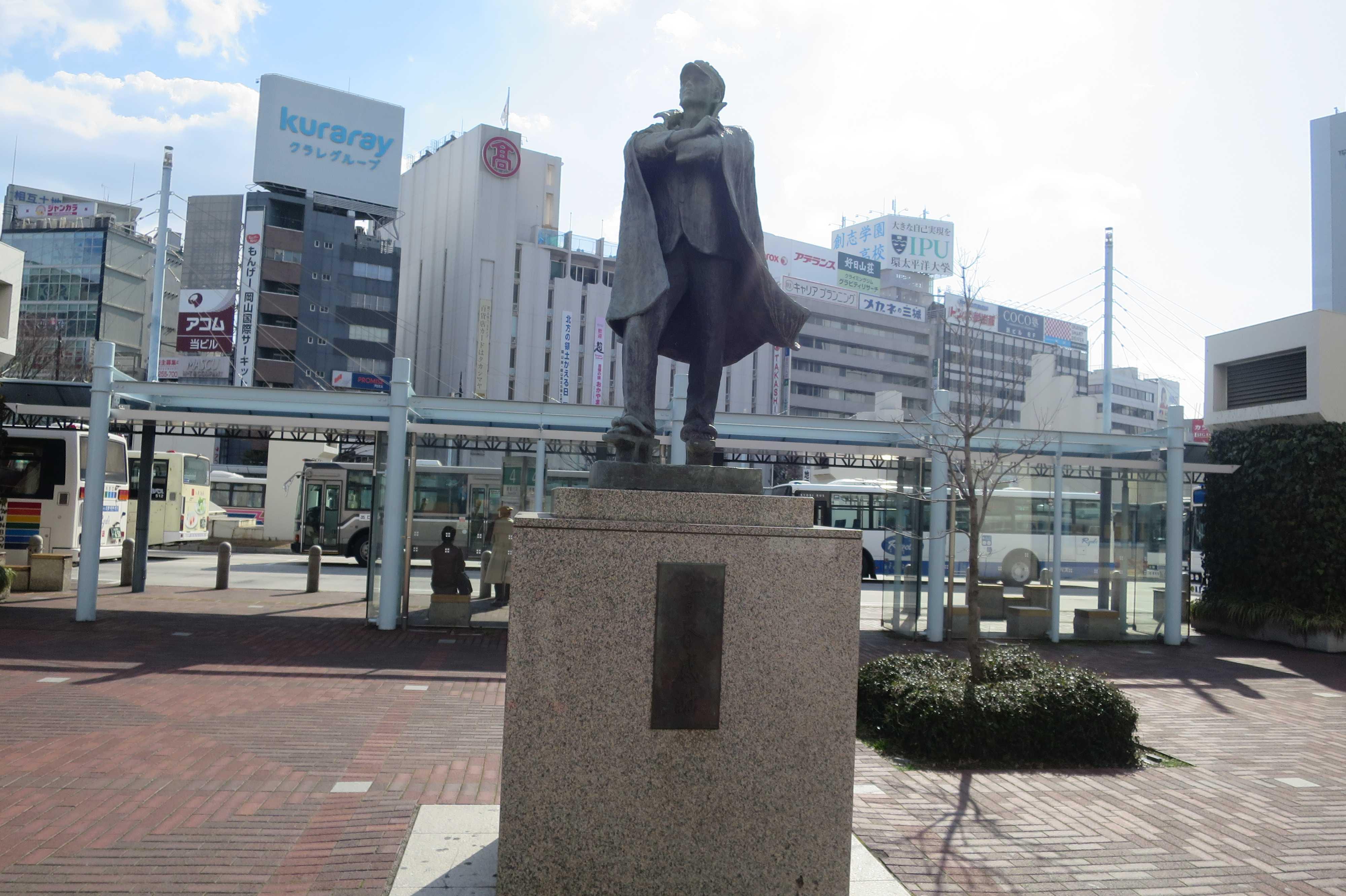 岡山駅前 - 台座に「青春感謝」と刻まれた高ゲタ黒マントの六高生記念像。