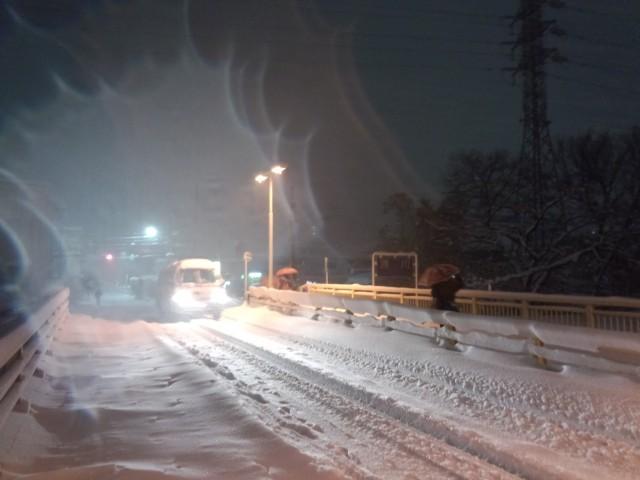 大雪と車のヘッドライト