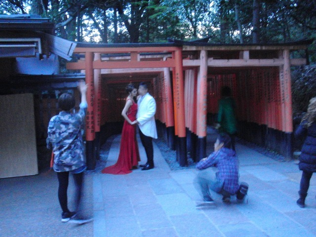 京都伏見稲荷大社で結婚記念写真を撮影するアジアのカップル