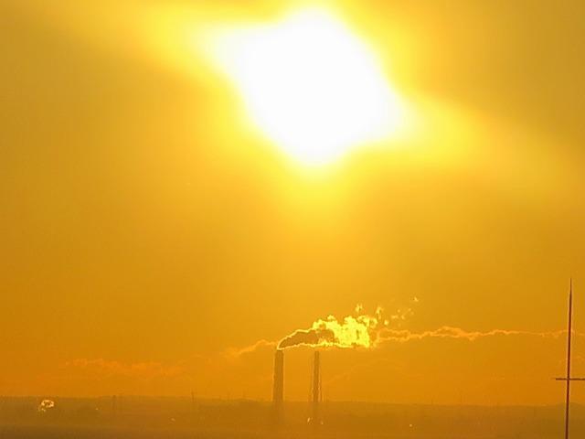 煙を吐く煙突とオレンジ色の朝日