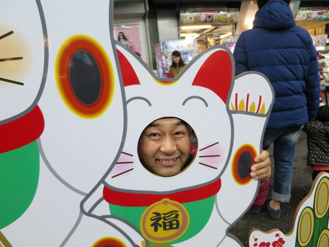 招き猫の顔ハメ看板で記念撮影する村内伸弘