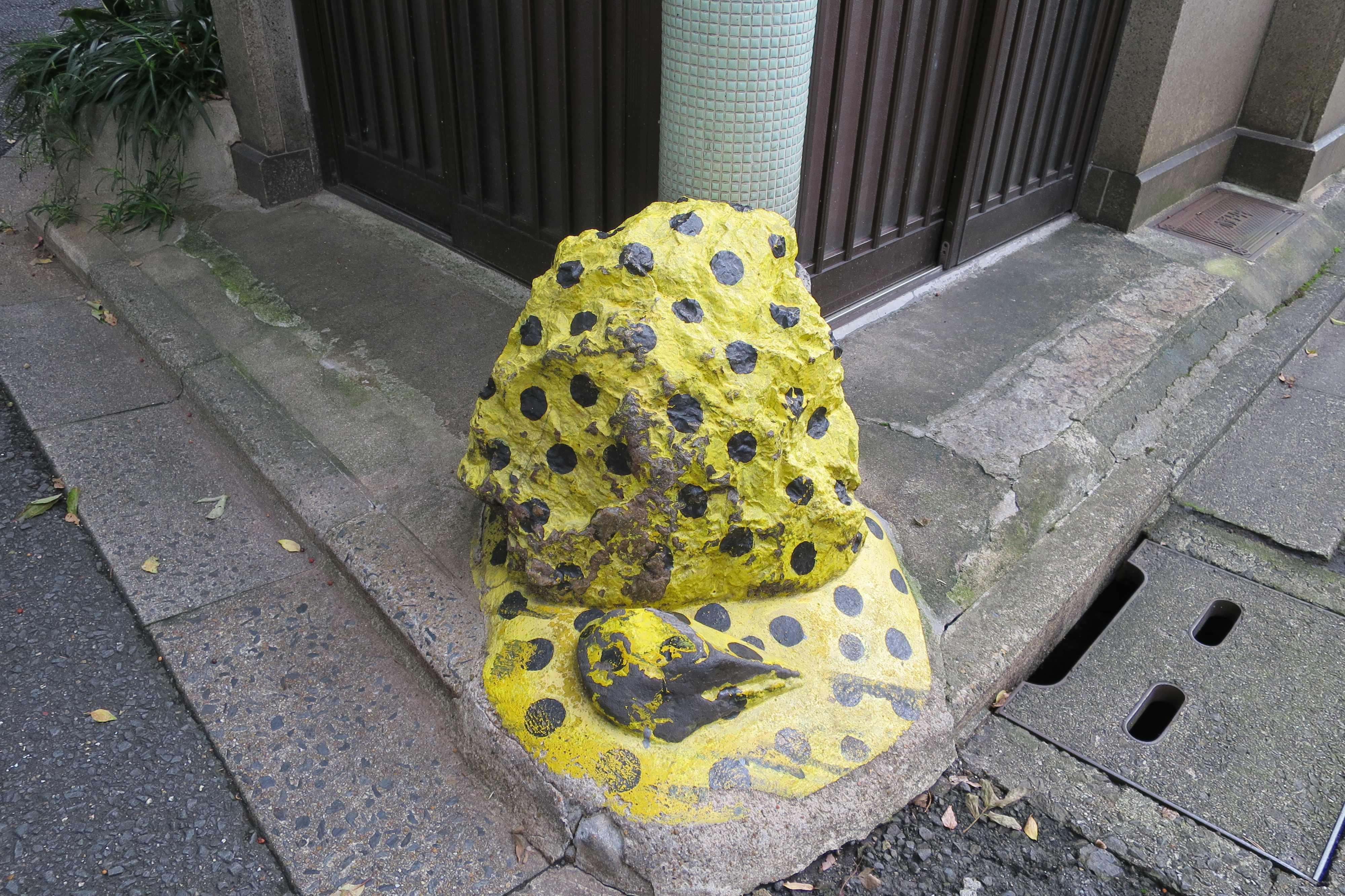京都・五条楽園 - 水色の豆タイル装飾の柱と黄色と黒のガードレール代りの石