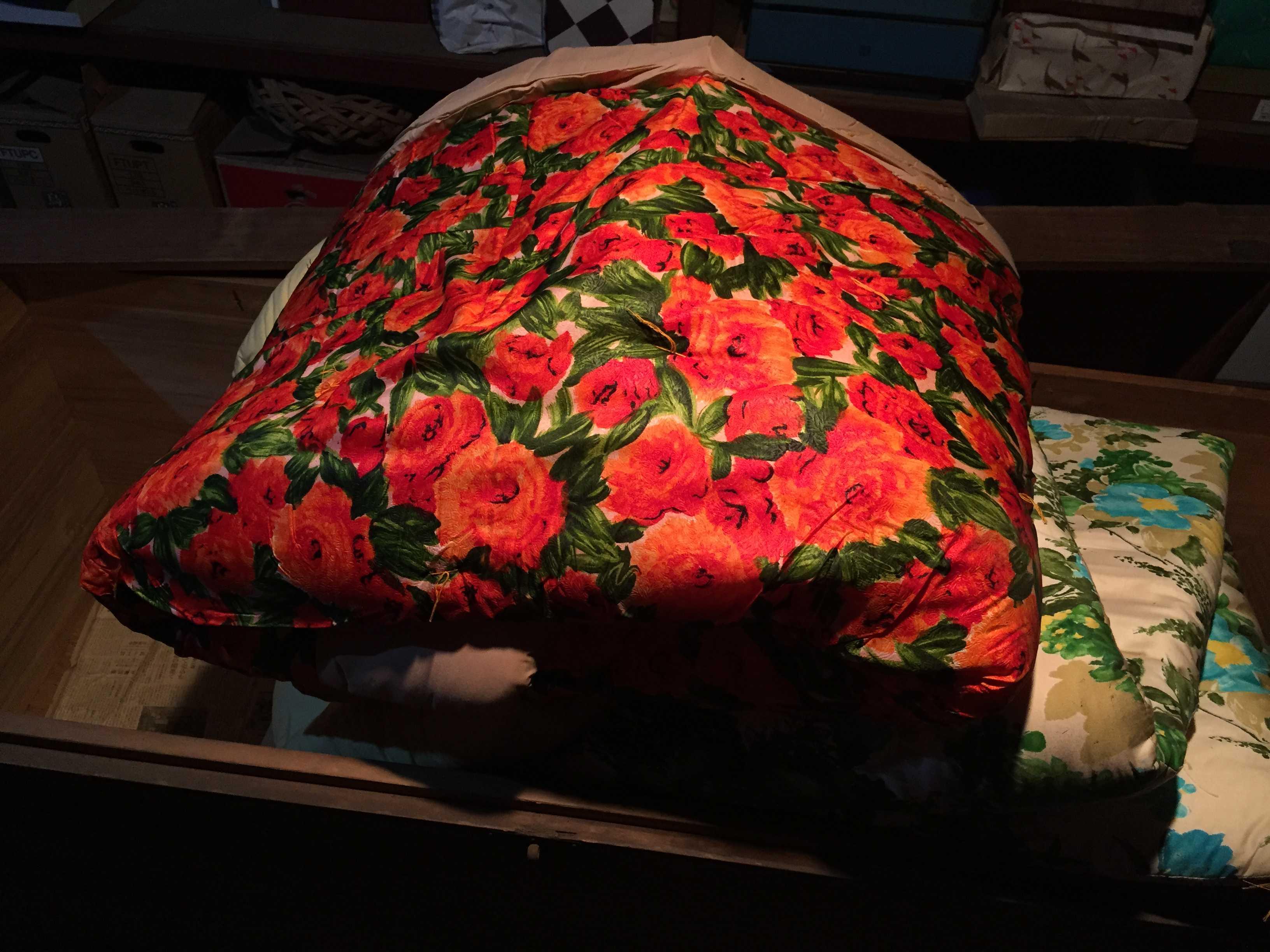 倉庫の照明に照らされた赤い薔薇の掛け蒲団