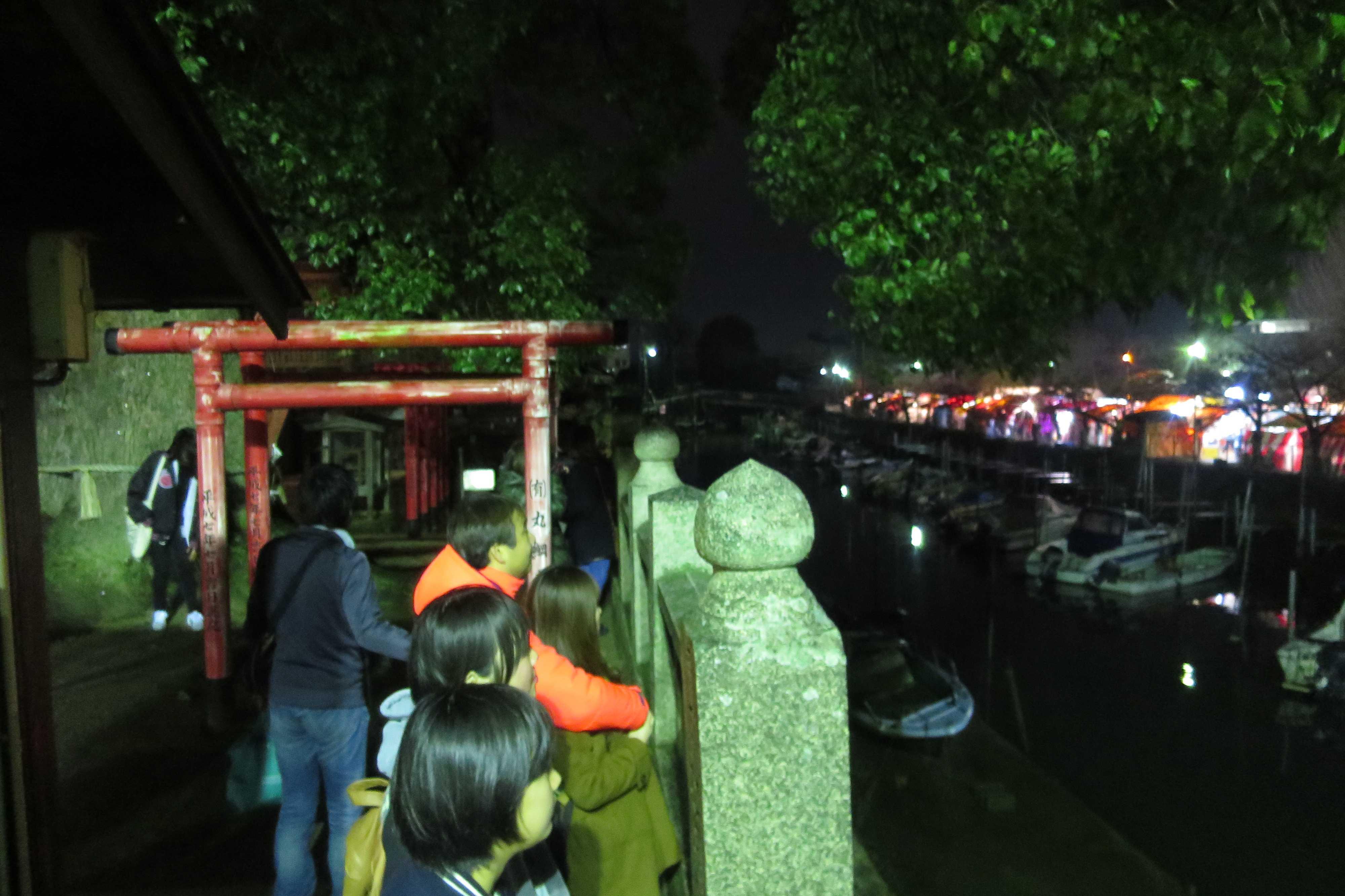 西大寺・稲荷神社の鳥居の前で会陽冬花火を眺める人たち