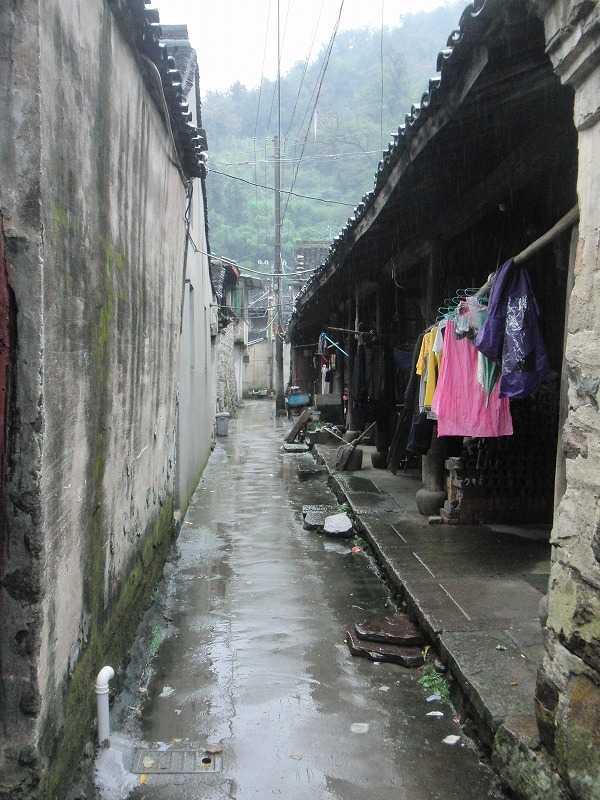 中国・天童村 濡れた黒瓦屋根と人間らしい路地