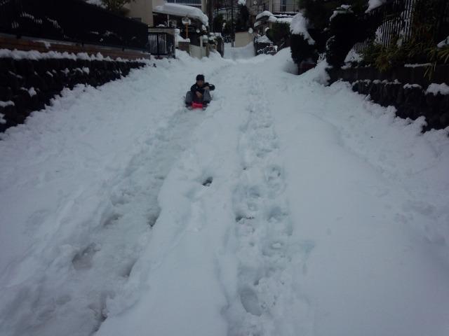 大雪翌日、そりであそぶ子供