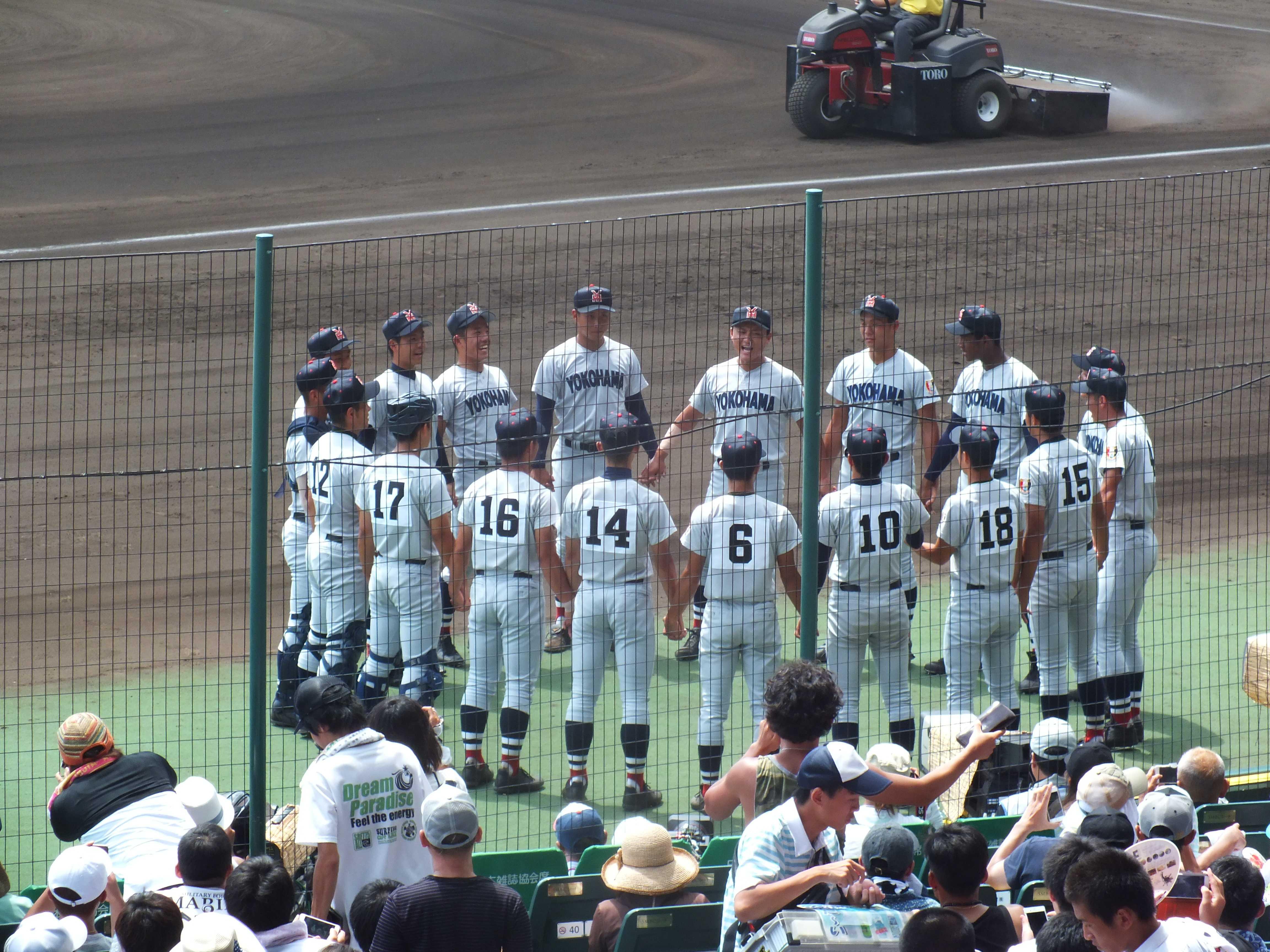 ベンチ前で円くなり互いに手を取り合う横浜高校ナイン