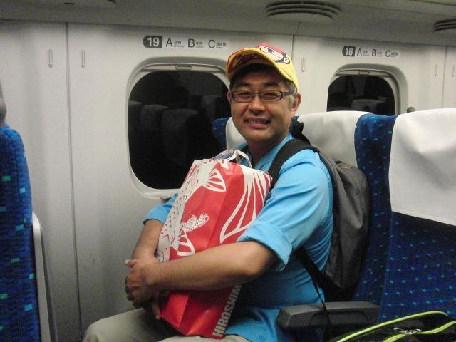 菊地キャップを被る新幹線の中の村内伸弘