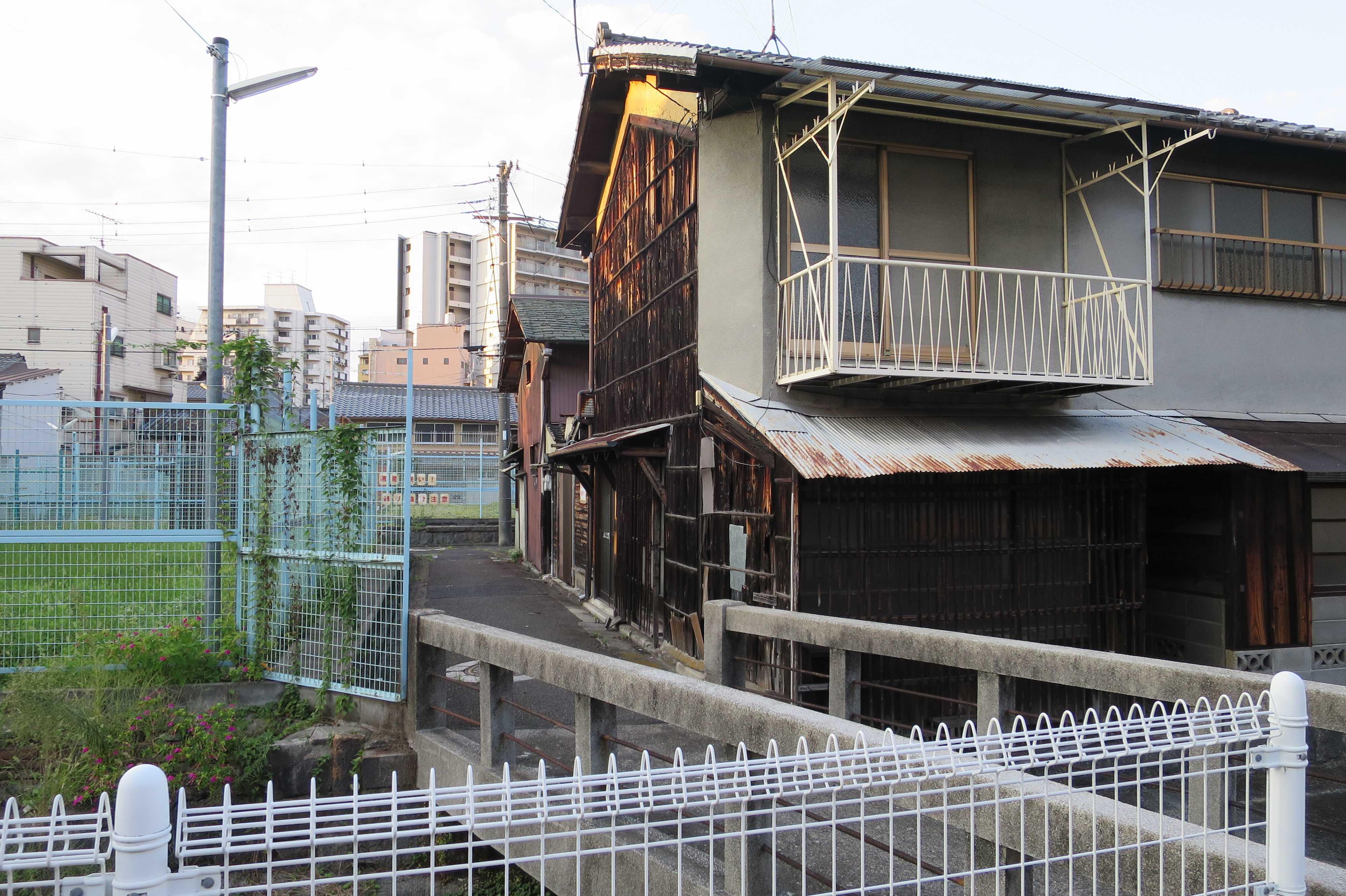 京都・崇仁地区 - 金網フェンスと夕陽に照らされた板塀