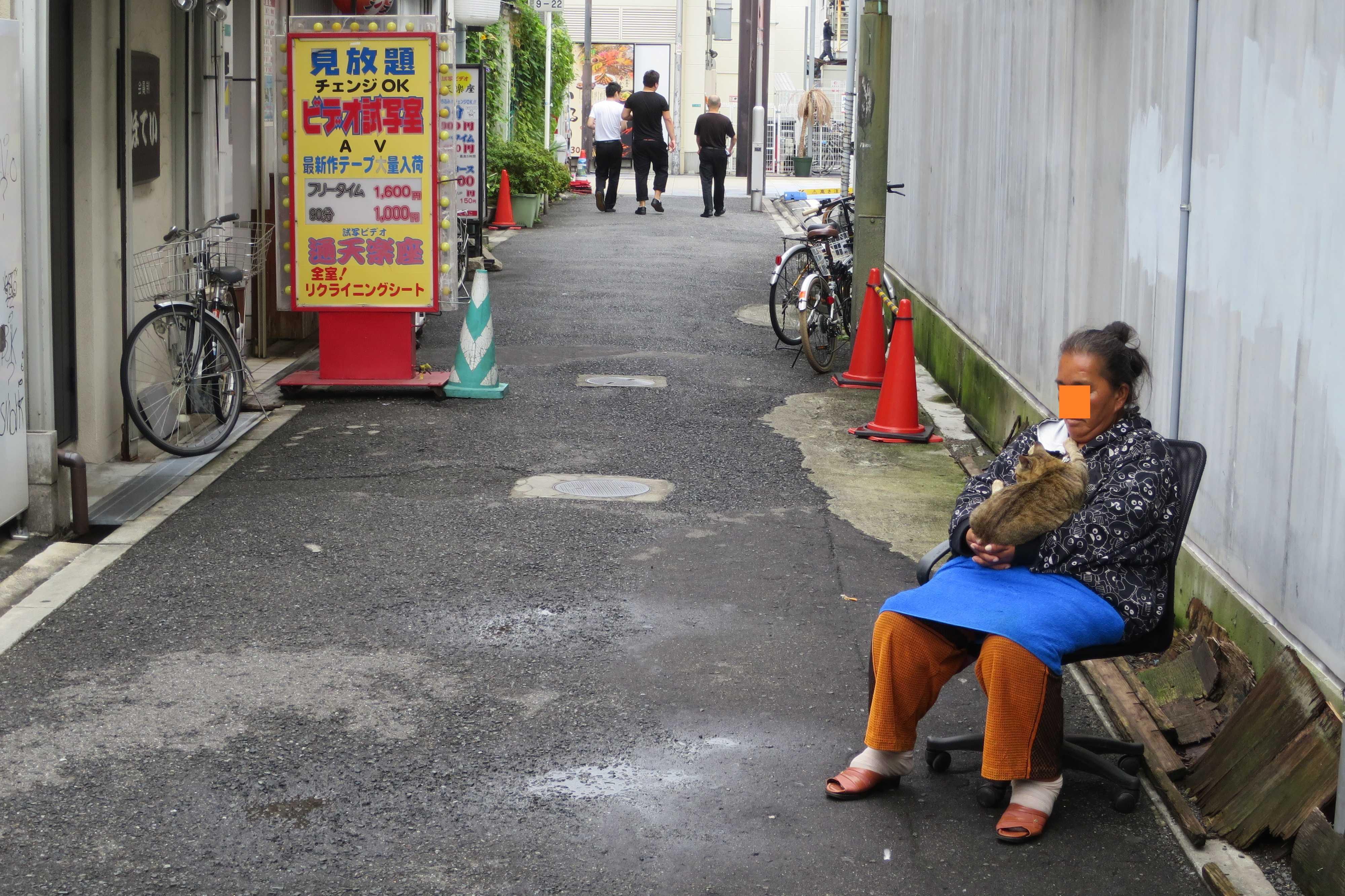 猫を抱きながら朝寝(朝昼寝?)するおばさん - 大阪新世界